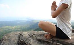 妇女在山峰峭壁的实践瑜伽 图库摄影