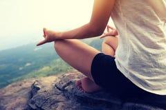 妇女在山峰峭壁的实践瑜伽 免版税库存图片