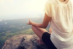 妇女在山峰峭壁的实践瑜伽 免版税图库摄影