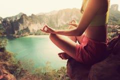 妇女在山峰峭壁的实践瑜伽 免版税库存照片