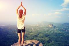 妇女在山峰峭壁的实践瑜伽 库存照片
