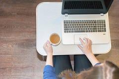 妇女在工作场所在家使用一台膝上型计算机 图库摄影