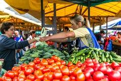 妇女在市场成熟菜,葱,胡椒,黄瓜,绿色卖 免版税库存图片