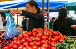妇女在市场成熟菜,葱,胡椒,黄瓜,绿色卖 免版税图库摄影