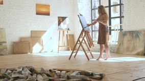 妇女在帆布的艺术家油漆在画架和举行调色板在艺术车间 股票视频