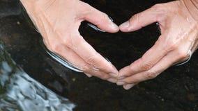 妇女在干净和清楚的水中递做心脏形状 免版税图库摄影