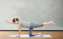 妇女在平衡的桌里的做瑜伽摆在席子 免版税库存图片