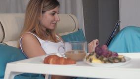 妇女在床上使用一台膝上型计算机并且临近到她的盘子用早餐咖啡和甜点 股票视频