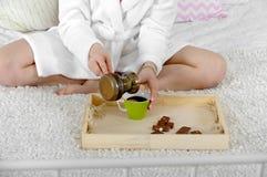 妇女在床上坐倾吐咖啡罐 免版税库存图片