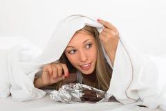 妇女在床上的吃巧克力 免版税库存图片