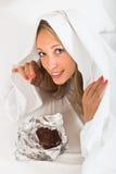 妇女在床上的吃巧克力 免版税库存照片