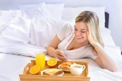 妇女在床上的吃早餐 库存图片