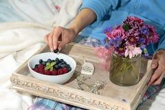 妇女在床上的吃果子 库存图片
