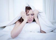 妇女在床上以不可能睡觉白色背景的失眠 免版税库存图片
