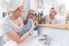 妇女在应用在刷子的卫生间里等高bronzer 免版税库存图片