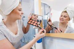 妇女在应用在刷子的卫生间里等高bronzer 免版税库存照片