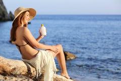 妇女在度假在申请在腿的海滩的遮光剂保护 图库摄影