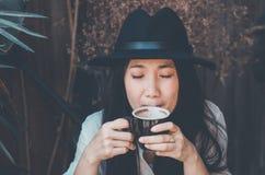 妇女在庭院里放松和饮用的咖啡 库存照片