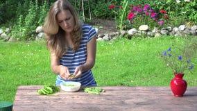妇女在庭院里去壳了在坐在桌上的板材的新鲜的豌豆 4K 影视素材