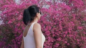妇女在开花的庭院里 股票录像