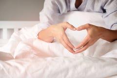 妇女在心脏形状用手显示一个姿态 免版税库存图片