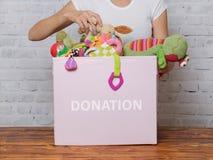 妇女在慈善商店准备捐赠玩具 免版税库存照片