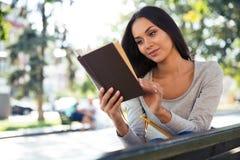 妇女在户外长凳的阅读书 图库摄影