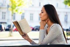 妇女在户外长凳的阅读书 库存图片