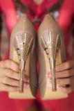 妇女在手上的拿着新的高跟鞋裸体鞋子 免版税库存图片