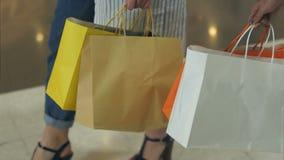 妇女在手上的拿着购物带来,走在购物在购物中心以后 影视素材