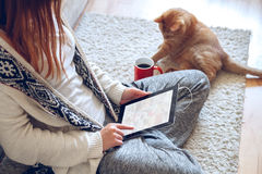 妇女在手中坐有片剂和咖啡的长沙发 库存照片
