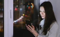 妇女在手机上的浏览网坐窗台在黑暗的夜 路背景 库存照片