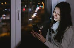 妇女在手机上的浏览网坐窗台在黑暗的夜 路背景 图库摄影