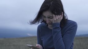 妇女在手机在恶劣天气读坏消息并且哭泣