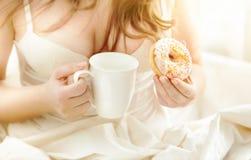 妇女在拿着多福饼和咖啡的床上在晴朗的早晨 免版税库存照片