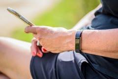 妇女在拿着有smartwatch的智能手机之外坐腕子 免版税库存图片