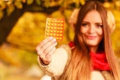 妇女在拿着维生素医学的秋天公园 免版税库存图片