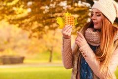 妇女在拿着维生素医学的秋天公园 免版税库存照片