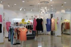 妇女在挂衣架的时装在商店 免版税库存图片