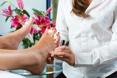 妇女在接受pedicure的钉子工作室 图库摄影