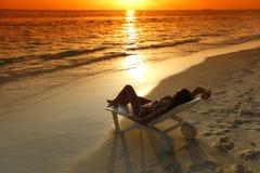 妇女在放松在海滩的轻便马车休息室 免版税库存照片
