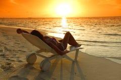 妇女在放松在海滩的轻便马车休息室 库存图片