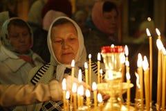 妇女在教会里 相信的祖母 有一个蜡烛的年长妇女 免版税库存照片