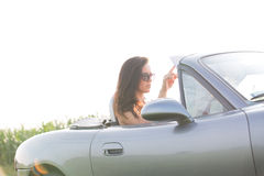 妇女在敞篷车的读书地图反对清楚的天空在晴天 免版税库存图片