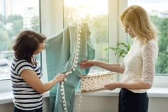 妇女在新的家选择织品和辅助部件帷幕的 免版税库存照片