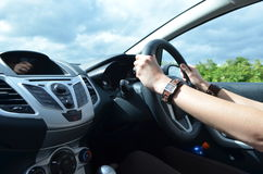 妇女在方向盘的` s手,驾驶在右边的一辆汽车 免版税库存图片