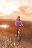 妇女在日落的骑马周期在河背景 免版税图库摄影