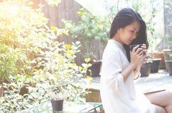 妇女在早晨庭院里喝咖啡 免版税库存照片