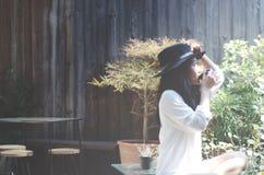 妇女在早晨饮用的咖啡的庭院里 库存图片