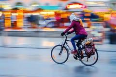 妇女在晚上骑一辆自行车在城市 免版税库存照片